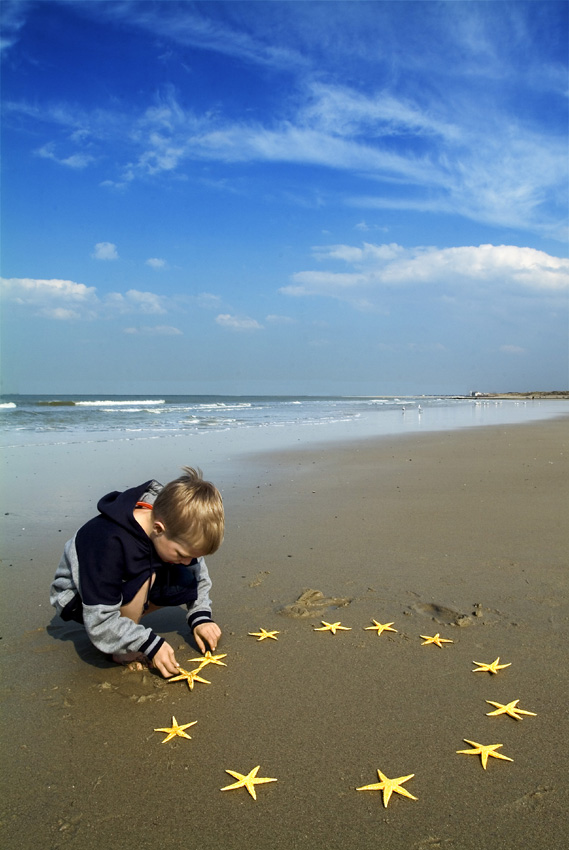 photo of boy on beach arranging the 12 EU stars in a circle