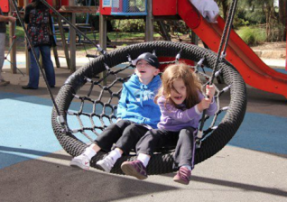 Inclusive playgrounds. Kids on swing. Photo. Touched by Olivia Foundation