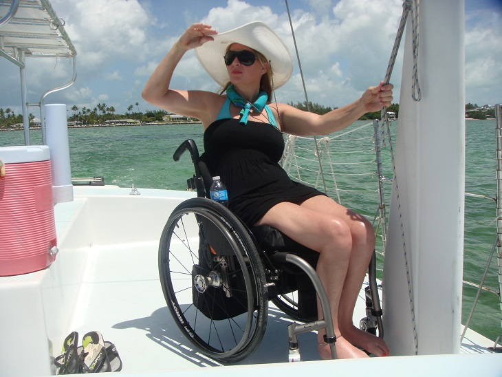 Image of lady wheelchair user on a sailboat looking to the distance