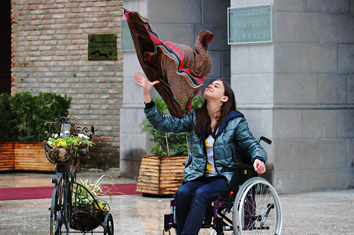 Image of girl in wheelchair throwing shawl in the air