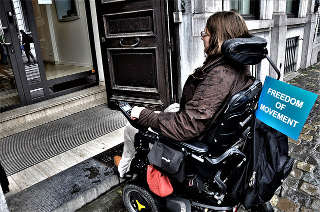 Photo of wheelchair user approaching building entrance with steps