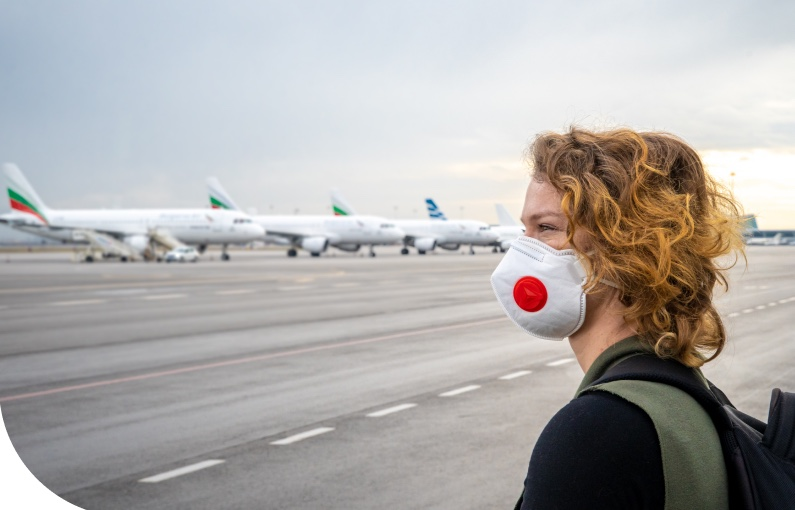 image of woman wearing facemask looking at line of aeroplanes