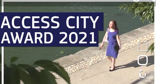 Image of blind female with white stick walking along waterfront. Text Access City Award 2021